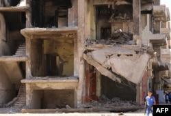 Một cậu bé Syria mang một khẩu súng đồ chơi đi qua một tòa nhà bị phá hủy ở thành phố Qamishli, ngày 13 tháng 9 năm 2016.