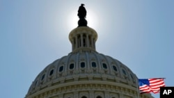 FILE - The US flag flies next to the Capitol in Washington, as Congress and the Obama Administration continue work to open the government and raise the debt ceiling.