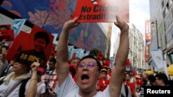 Seorang demonstran mengacungkan poster dalam unjuk rasa menuntut otoritas menghapus rancangan undang-undang ekstradisi dengan China, di Hong Kong, 9 Juni 2019.