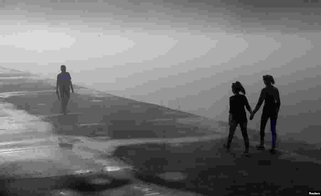 People walk along a foggy embankment of the Yenisei river in the Siberian town of Divnogorsk, Russia.