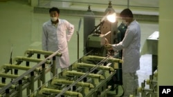 Iranian technicians work at a facility making uranium fuel in this file photo.