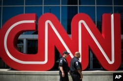 FILE - Security guards walk past the entrance to CNN headquarters in Atlanta.