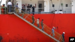 FILE - Afghan migrants walk down the stairway of a tanker that rescued them at a port in Cilegon, Banten province, Indonesia, Apr. 9, 2012. Indonesia said it had rescued 120 Afghan migrants from a leaking wooden ship headed to Australia after receiving a distress call from the ship's captain on Sunday and went to their aid.