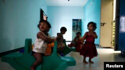 Baby girls play inside the Life Line Trust orphanage in Salem in the southern Indian state of Tamil Nadu, June 20, 2013.