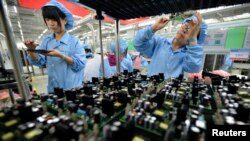 Nhân viên Trung Quốc làm việc trên một dây chuyền sản xuất tại nhà máy FiberHome Technologies Group ở Vũ Hán, tỉnh Hồ Bắc.
