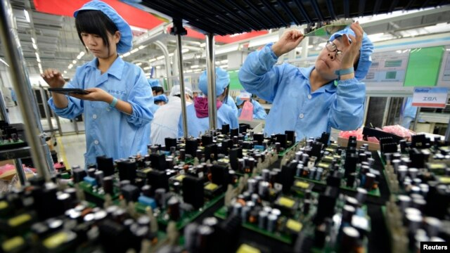 FILE - Employees are seen working on a FiberHome Technologies Group factory production line in Wuhan, Hubei province, China, July 27, 2015.