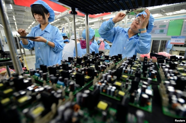 FILE - Employees work on a FiberHome Technologies Group factory production line in Wuhan, Hubei province, China, July 27, 2015.