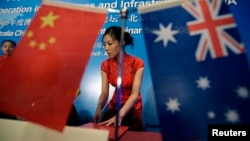 FILE - A stewardess arranges documents before a seminar of Australia China bilateral cooperation in resources and infrastructure in West Australia, in Beijing.