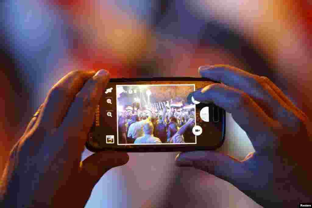 Seorang demonstran menggunakan ponselnya untuk mengambil foto di sela-sela demo menentang kualitas pelayanan dasar yang buruk, pemadaman listrik dan tuntutan untuk mempersidangkan politisi-politisi yang korupsi di Baghdad, Irak.