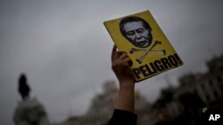 """A man holds a sign with a portrait of Peru's jailed President Alberto Fujimori and the Spanish word """"Danger"""" during a march in Lima, Peru, July 7, 2017. Peruvian President Pedro Kuczynski said Friday that a group of doctors will help him determine whether to release ex-president Alberto Fujimori, sentenced to 25 years prison, with a medical pardon."""