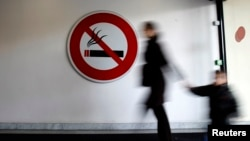 "FILE - A woman and child walk past a ""No Smoking"" sign. A Yale-led study has found that nicotine exposure during pregnancy can trigger long-term genetic changes in unborn babies."