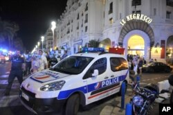 A police car is parked near the scene of an attack after a truck drove on to the sidewalk and plowed through a crowd of revelers who'd gathered to watch the fireworks in the French resort city of Nice, southern France, Friday, July 15, 2016.