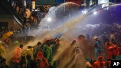 Pro-democracy demonstrators face water canons as police try to clear the protest venue in Bangkok, Thailand.