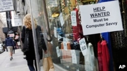 FILE - A shopper walks past a store with a help wanted sign in the window in New York, Oct. 1, 2015. The final major economic report of the Obama administration is expected to show continued modest economic growth.