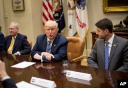FILE - President Donald Trump, with Senate Majority Leader Mitch McConnell of Kentucky, left, and House Speaker Paul Ryan of Wisconsin, speaks during a meeting with congressional leaders in the Roosevelt Room of the White House in Washington, June 6, 2017