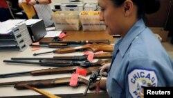 """Viên cảnh sát Chicago đang kiểm kê súng thu được từ sự kiện """"Đổi súng lấy thẻ quà tặng"""", theo đó mỗi cây súng được giao nộp lại cho cảnh sát ở Illinois, Chicago sẽ nhận được một thẻ quà tặng, ngày 28/5/2016."""