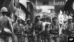 FILE - Japanese soldiers, their rifles shouldered, are seen as they march into the city and port of Ningbo, in southeastern China, May 14, 1941.