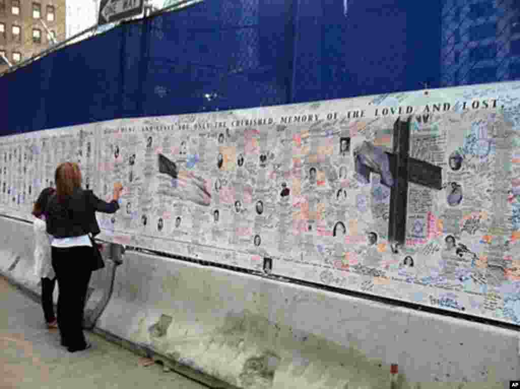 A woman traces a name on a wall of names and pictures outside the World Trade Center memorial, September 11, 2011 (VOA - C. Presutti)