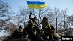 Anggota pasukan Ukraina dan kendaraan lapis baja berpatroli di dekat Debaltseve pasta penandatanganan kesepakatan gencatan senjata di Minsk (12/2).