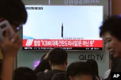 FILE - In this May 21, 2107, photo people watch a TV news program showing a file image of a missile launch conducted by North Korea, at the Seoul Railway Station in Seoul, South Korea.