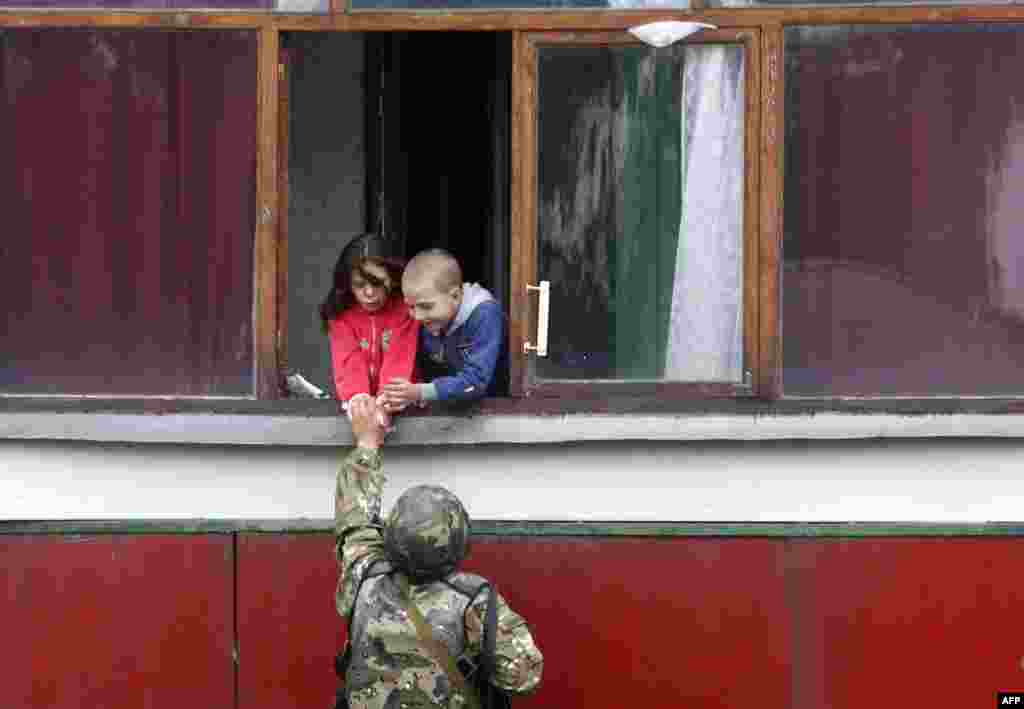 A Ukrainian soldier gives sweets to children in Popasna, Lugansk region, recently freed by Ukrainian forces from pro-Russia militants.
