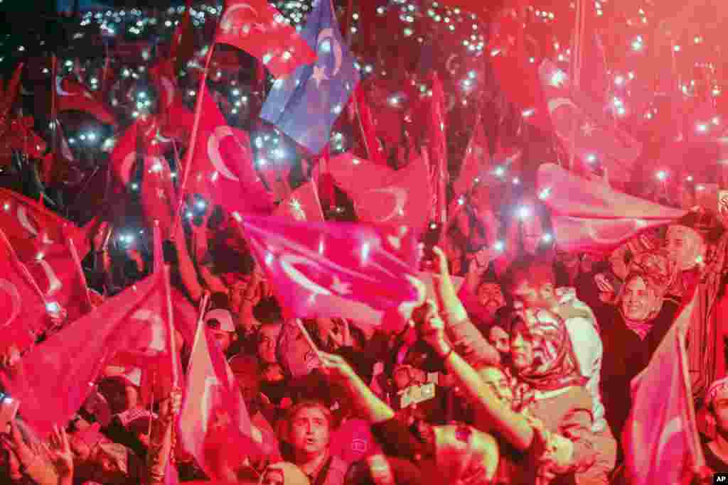 Turkish people wave flags of their country and use the lights of their cell phones during the speech of President Recep Tayyip Erdogan in Istanbul, Aug. 7, 2016.