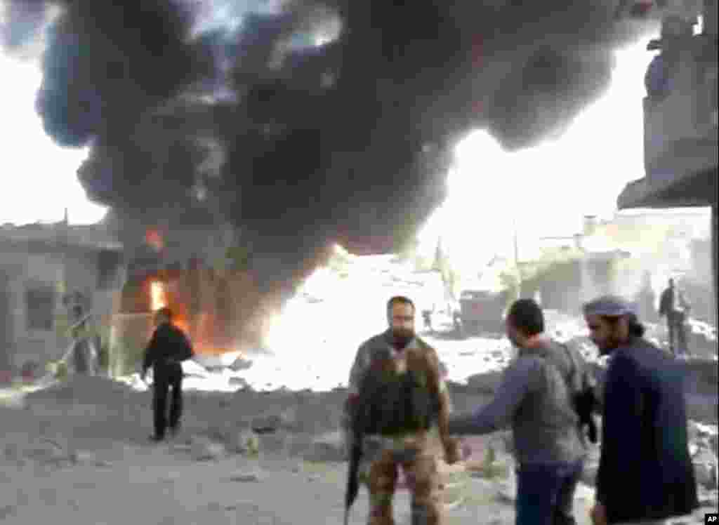 Syrians inspect damage and look for victims moments after an airstrike by Syrian warplanes in Ras al-Ayn, Syria, November 12, 2012, in an image taken from video.