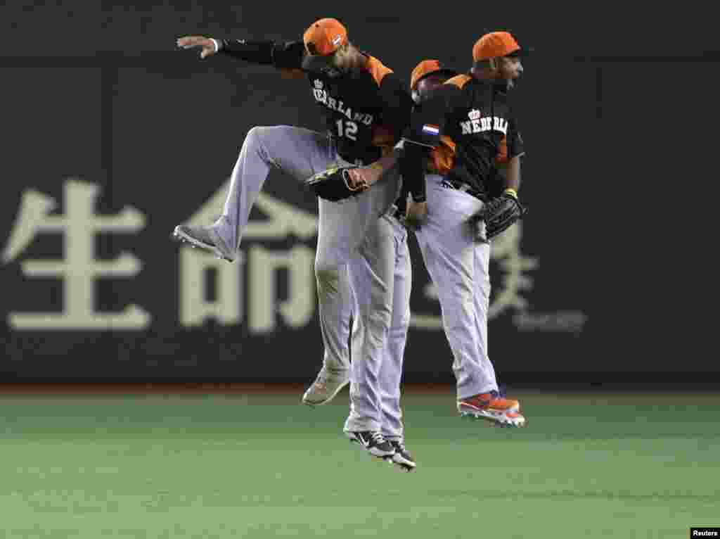 Netherlands' Wladimir Balentien (R), Roger Bernadina (C) and Kalian Sams celebrate after defeating Cuba at the World Baseball Classic second round game in Tokyo, Japan.