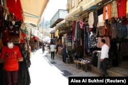 Orang-orang berjalan melewati toko-toko di sebuah pasar di Salt, Yordania saat UNESCO mendaftarkan kota itu sebagai Situs Warisan Dunia, 28 Juli 2021. (Foto: REUTERS/Alaa Al Sukhni)