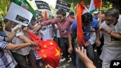 Para demonstran India membakar bendera China dalam protes di New Delhi (1/5) setelah tentara China dilaporkan melanggar perbatasan dan masuk ke wilayah India di Ladakh di kawasan Himalaya.