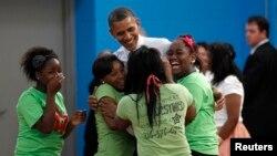 Jóvenes abrazan al presidente Obama durnate una visita a un colegio en Cleveland.
