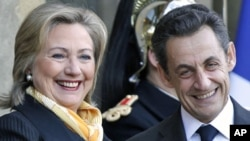 U.S. Secretary of State Hillary Clinton (L) is greeted by France's President Nicolas Sarkozy upon her arrival at the Elysee Palace in Paris, March 14, 2011