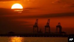 امریکہ کی ریاست مسی سپی کی گلف پورٹ کے پسِ منظر میں سورج غروب ہو رہا ہے۔ (فائل فوٹو)
