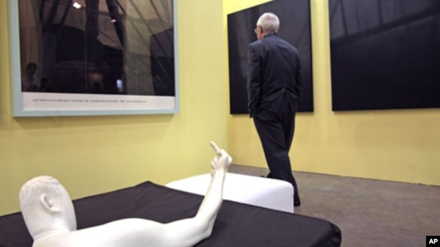 "A man walks past the sculpture titled ""Marble Arm"" by Chinese dissident artist Ai Weiwei at Hong Kong International Art Fair, May 25, 2011"