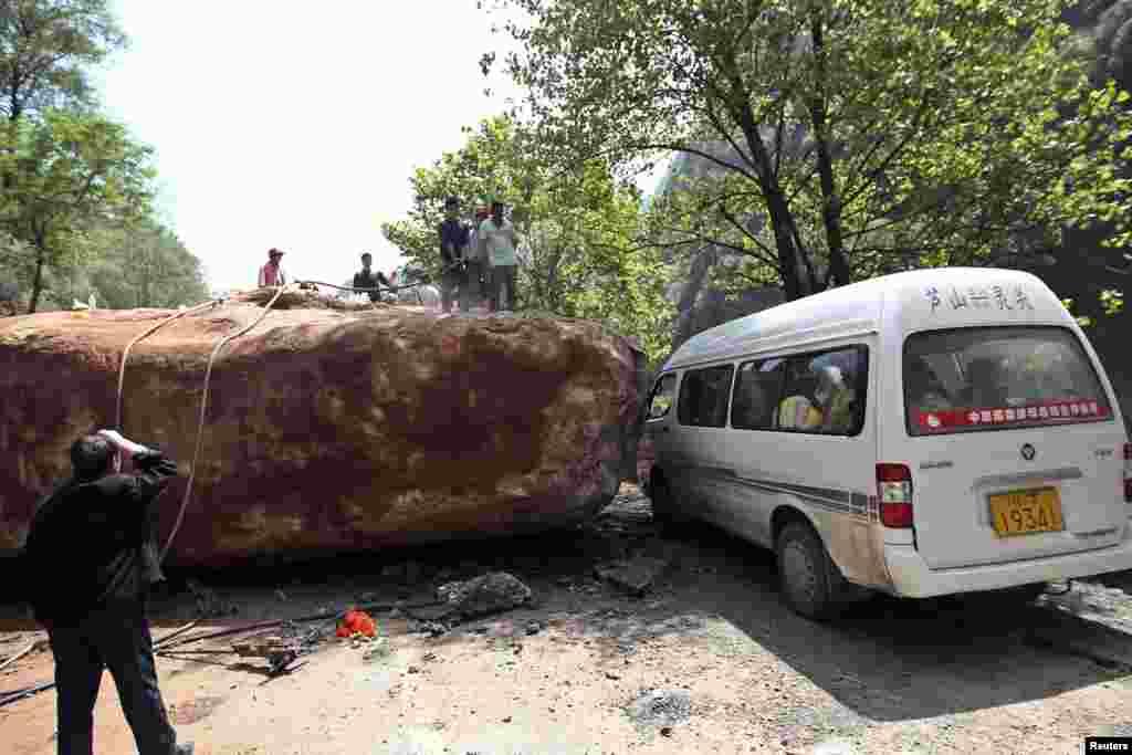 2013年4月20日星期六,中國四川省雅安市蘆山縣發生里氏7級強烈地震。在龍門鄉人們站在一輛被倒塌的大石頭阻擋的車前。