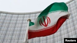 FILE - An Iranian flag flutters in front of the International Atomic Energy Agency (IAEA) headquarters in Vienna, Austria, Jan. 15, 2016.