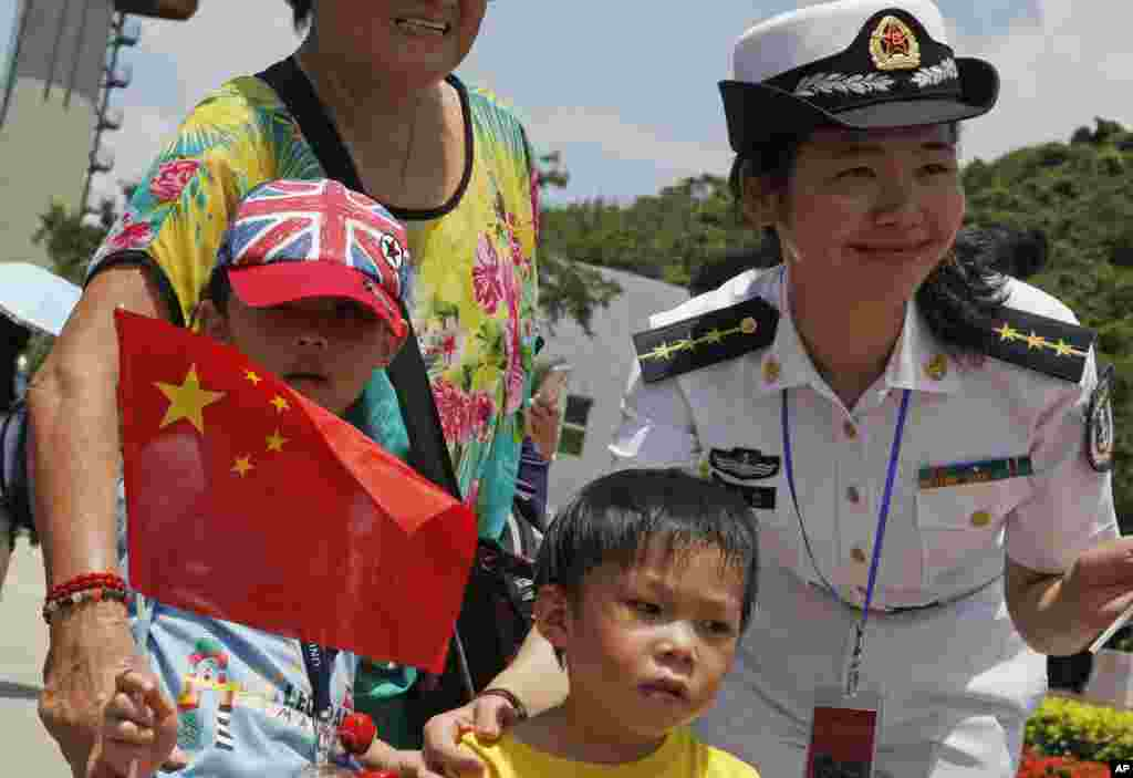 Visitors pose with Chinese People's Liberation Army (PLA) personnel during opening day of Stonecutter Island Navy Base to mark the 18th anniversary of the Hong Kong handover to China, in Hong Kong, July 1, 2015.