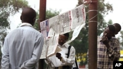 "FILE - People read Congolese newspapers hung up by newspaper vendors in Kinshasa, the capital of the Congo, July 30, 2002. Journalists in the region would observe a ""day without the press"" on Thursday, in honor of a TV reporter killed Tuesday."