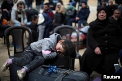 A girl sleeps on a suitcase as she waits with her family for a travel permit to cross into Egypt through the Rafah border crossing after it was opened by Egyptian authorities for humanitarian cases, in the southern Gaza Strip February 8, 2018.