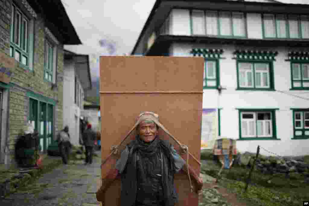 A Nepalese laborer transports a piece of plywood at Lukla, Nepal.