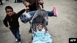 Une syrienne tenant une prothèse de jambe de son mari sur la poussette de leur bébé alors qu'ils arrivent avec d'autres migrants et des demandeurs d'asile vers le port du Pirée, le 21 Octobre 2015.