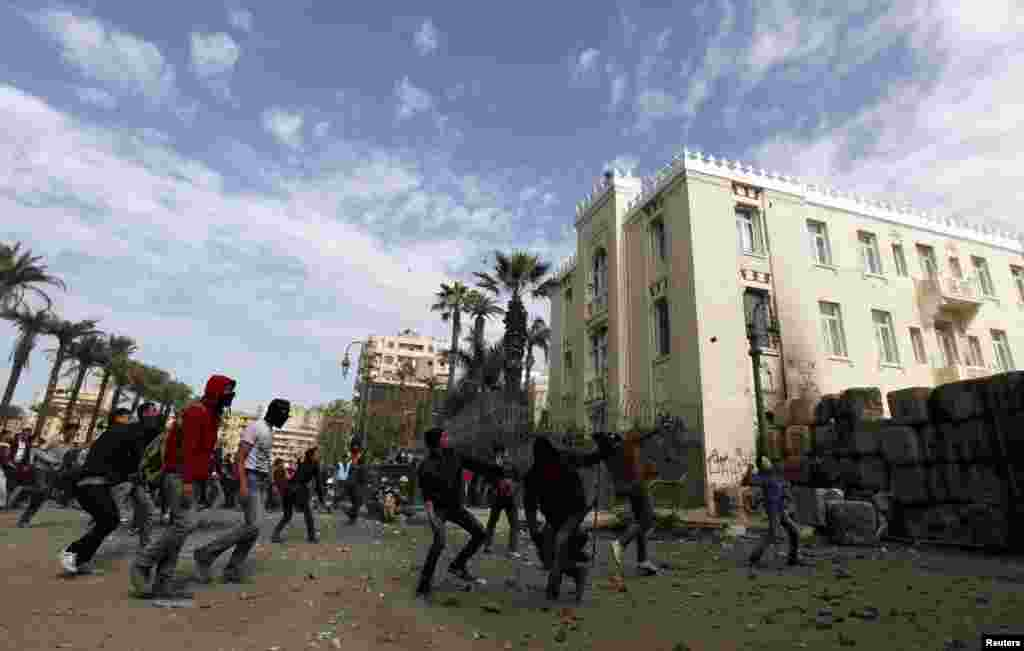 Protesters opposing Egyptian President Mohamed Morsi throw stones towards riot police during clashes near Tahrir Square, Cairo, Egypt, January 25, 2013.