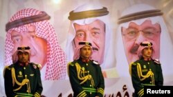 Saudi royal guards stand on duty in front of portraits of King Abdullah bin Abdulaziz (R), Crown Prince Salman bin Abdulaziz (C) and second deputy Prime Minister Muqrin bin Abdulaziz.