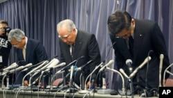 Pemimpin dan CEO Suzuki Motor Corp. Osamu Suzuki, (tengah), bersama presiden perusahaan itu, Toshihiko Suzuki (kanan) dan wakilnya Osamu Honda melmbungkukkan badan mereka saat memulai konferensi pers di Tokyo (18/6).