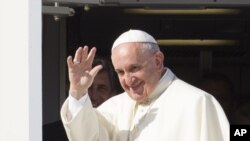 Pope Francis waves to reporters at Rome's
