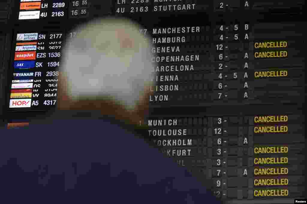 A passenger looks at the flight information screen during a regional strike at Zaventem Airport in Brussels, Belgium, Dec. 8, 2014.