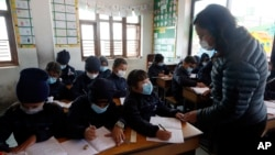 Students and a teacher wear masks as a precautionary measure at Matribhumi school in Bhaktapur, Nepal, Wednesday, Jan. 29, 2020. There has been one confirmed case of a new coronavirus infection in the Himalayan country. (AP Photo/Niranjan Shrestha)