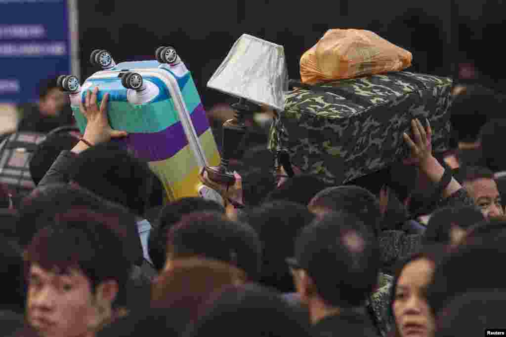 People carry their belongings at the main railway station in Guangzhou, Guangdong province, China, as travel for the annual Chinese Lunar New Year and Spring Festival holidays continues.