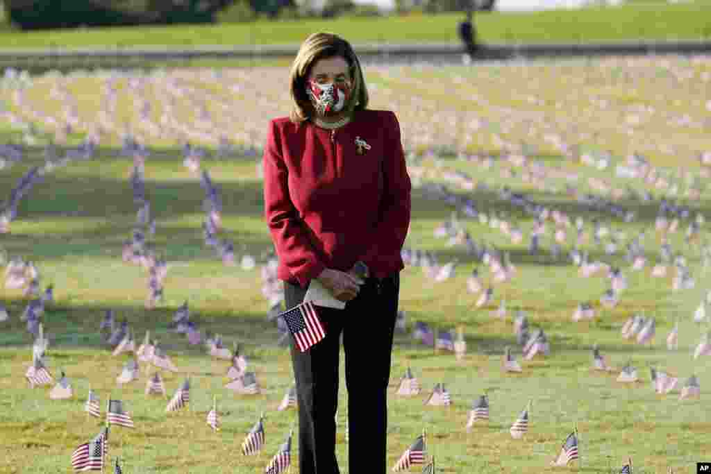House Speaker Nancy Pelosi looks at small flags placed on the grounds of the National Mall by activists from the COVID Memorial Project to mark the deaths of 200,000 lives lost in the U.S. to COVID-19, in Washington, D.C.