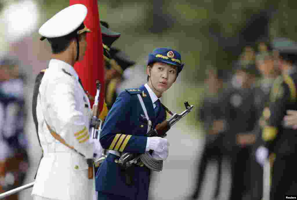A female member of the honor guard looks on ahead of a welcoming ceremony for Malaysia's Prime Minister Najib Razak outside the Great Hall of the People, in Beijing, China.